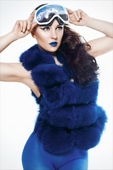 Woman's portrait with blue lipstick in a blue fur coat vest, leggings, and ski mack, in which snow and mountains are reflected.