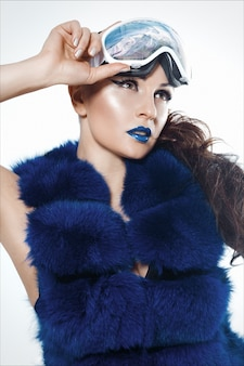 Woman's portrait with blue lipstick in a blue fur coat vest and ski mack, in which snow and mountains are reflected.
