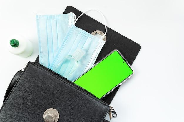 Женский кошелек с телефоном, антисептиком, медицинской маской и на белом фоне, телефон с зеленым экраном, хромакей, вид сверху, изолированный