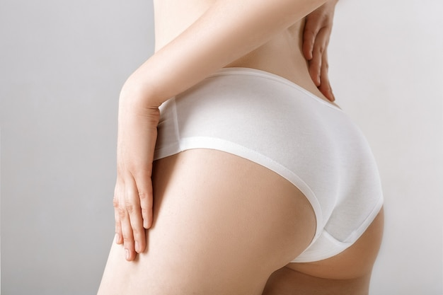Woman's rear in white lingerie on the grey
