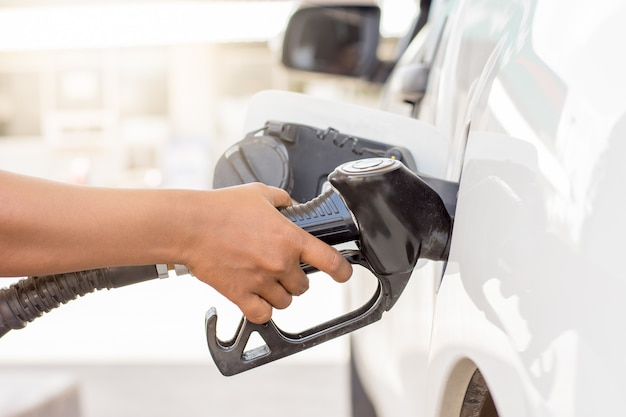 The woman's right hand holds the nozzle to refuel the white car