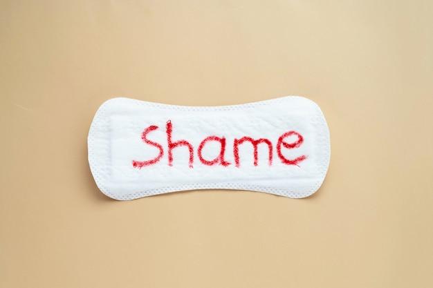 수치심이라는 단어가 있는 여성용 생리대. 월경 기간 동안 여성을 부끄러워하는 추상적 사회적 개념.