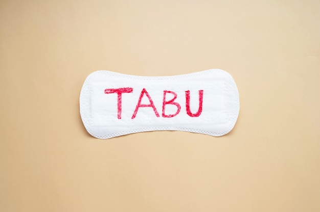 Woman's sanitary pad with word tabu. abstract social concept of fear of talking about menstrual period