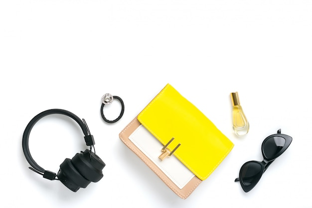 Женский набор аксессуаров желтая, бежевая сумочка, беспроводные наушники, духи, резинка для волос, черные солнцезащитные очки изолированные вид сверху плоская планировка