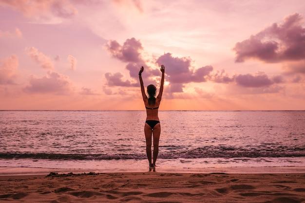 Силуэт женщины с поднятыми руками против спокойного пляжа заката. концепция свободы и хорошего самочувствия