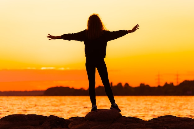 Силуэт женщины на закате, стоя на скале, глядя прямо с вытянутыми руками. концепция природы и красоты. оранжевый закат.
