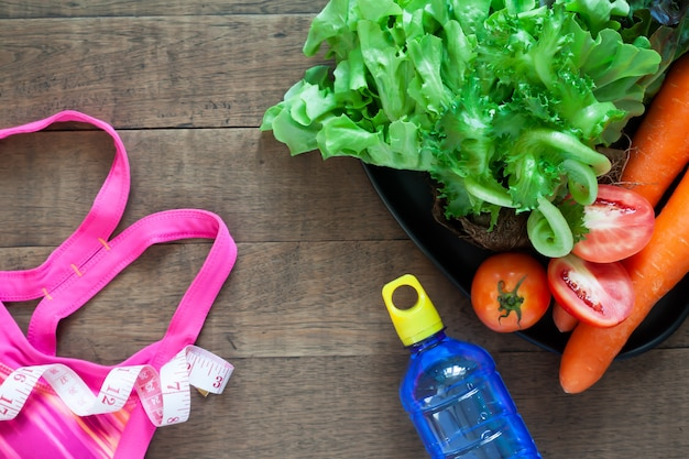 Woman's sport bra and healthy foods on wooden background
