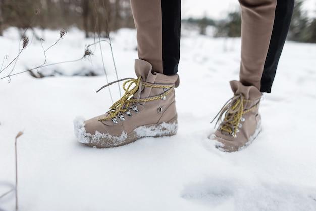 Женские стильные зимние коричневые теплые кожаные туфли. человек идет по зимнему лесу. крупный план мужских ног.