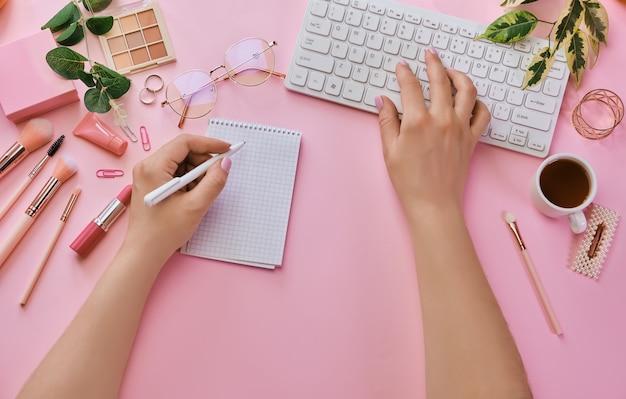 Женский стол с кофе, канцелярскими принадлежностями, розовыми кистями для макияжа, клавиатурой и ноутбуком. вид сверху с копией пространства