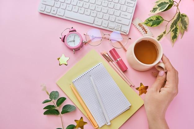 Женский столик с кофе, канцелярскими принадлежностями, розовыми кистями для макияжа, клавиатурой и блокнотом