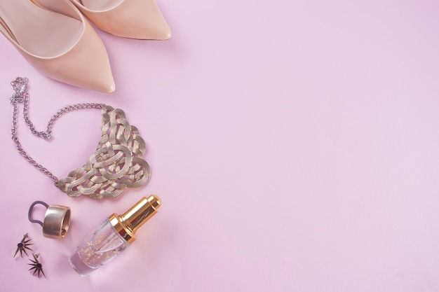 Woman's trendy accessories on pink background, top view