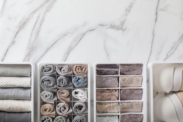 Женское нижнее белье, пижамы и носки аккуратно сложены и помещены в разделительную перегородку ящика-органайзера.