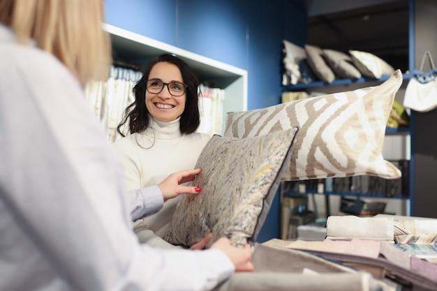 살롱 디자인 서비스 개념에서 장식용 베개를 보여주는 여성 세일즈맨