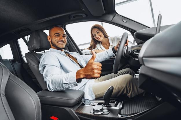 車のショールームで男性のクライアントに車を見せている女性の販売員