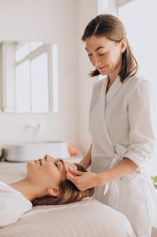 Woman in salon making beauty treatment with gua sha stone