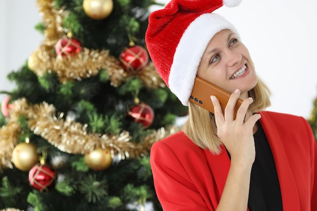 Woman in santa claus hat is talking on phone against background of christmas tree new year