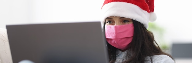 Woman in santa claus hat in protective medical mask smiles and looks into laptop computer.