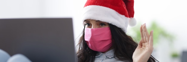 Woman in santa claus hat in protective medical mask smiles and waves welcomingly into laptop.