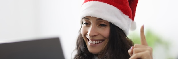 Woman in santa claus hat smiles holds thumbs up and looks into laptop computer.