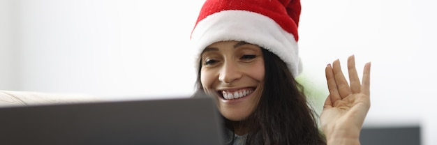 Woman in santa claus hat smiles and waves greeting into laptop computer.
