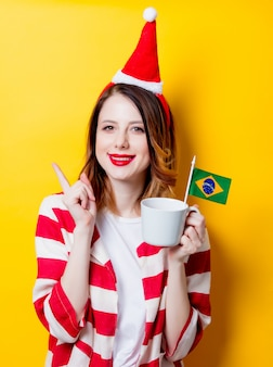 Woman in santa claus hat with brasil flag and cup