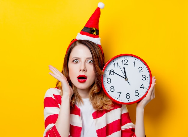 Woman in santa claus hat with clock