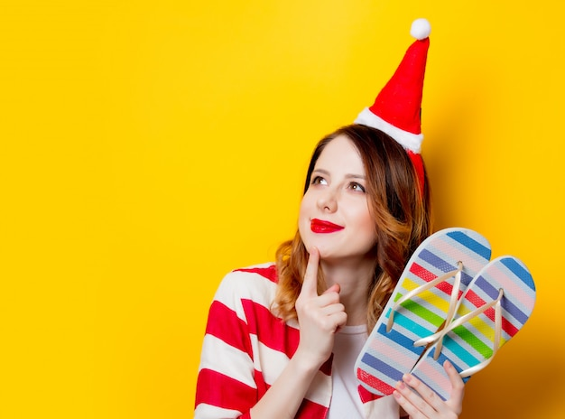 Woman in santa claus hat with flip flops