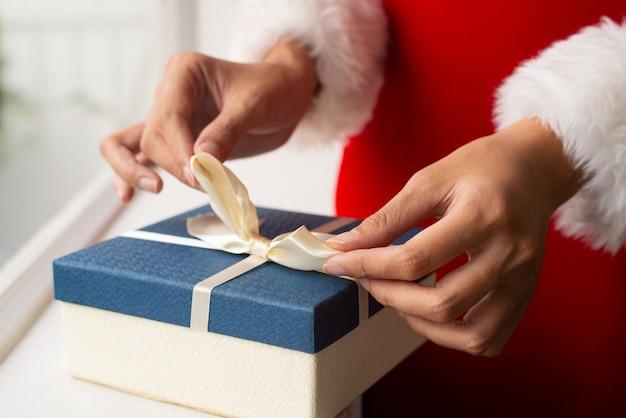 Woman in santa costume tying ribbon on top of present box