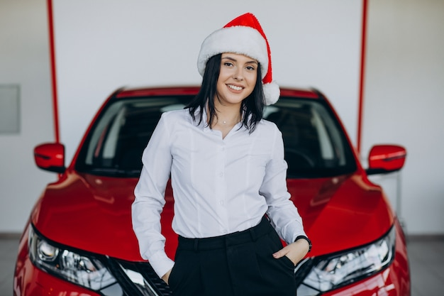 Donna in cappello della santa dall'auto rossa in uno showroom di auto