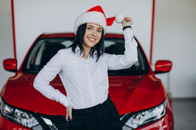 Woman in santa hat by the red car in a car showroom
