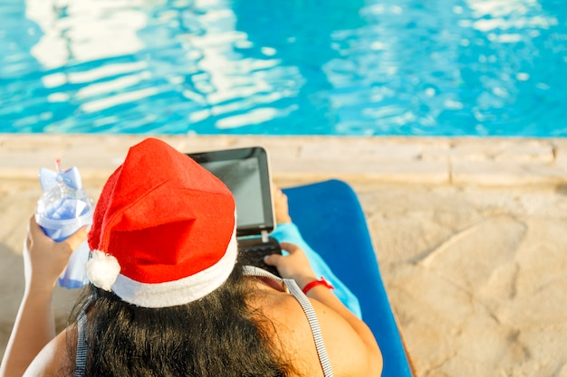 A woman in a santa hat congratulates online friends on a sun lounger by the pool during the christmas holidays next to a decorated christmas tree.