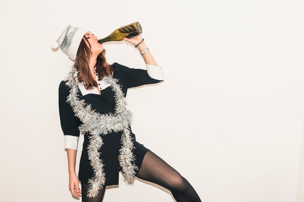 Woman in santa hat drinking champagne from bottle