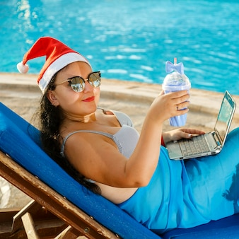 A woman in a santa hat drinks a cocktail
