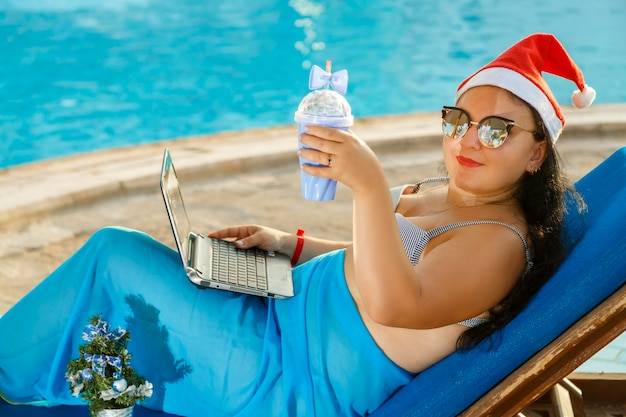 A woman in a santa hat drinks a cocktail on