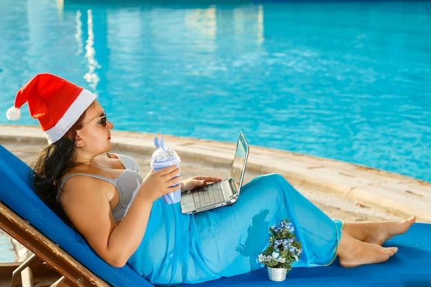 A woman in a santa hat drinks