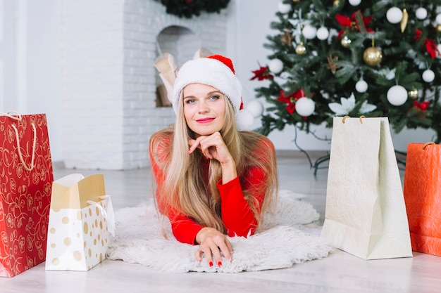 Woman in santa hat lying on floor