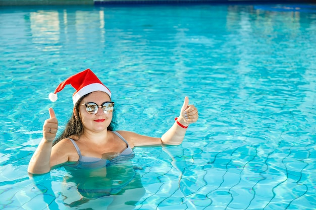 A woman in a santa hat in the pool celebrates christmas and shows her class with her hand.