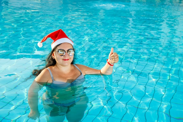 A woman in a santa hat in the pool during the new year and christmas holidays.