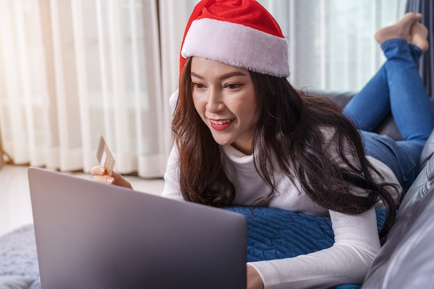 Woman in santa hat shopping online for christmas gift with laptop in living room