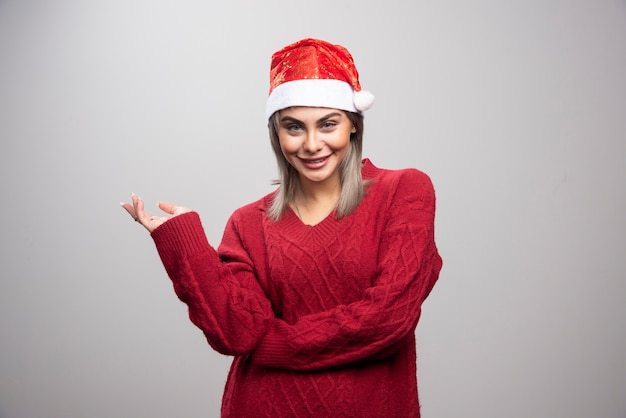 Woman in santa hat standing happily on gray background.