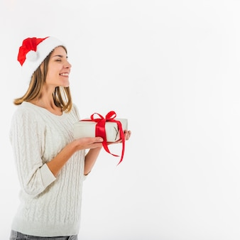 Woman in santa hat standing with gift box