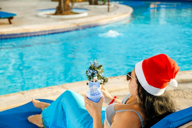 A woman in a santa hat and sunglasses and a swimsuit