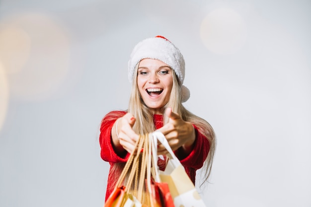 Woman in santa hat with colourful shopping bags in hands
