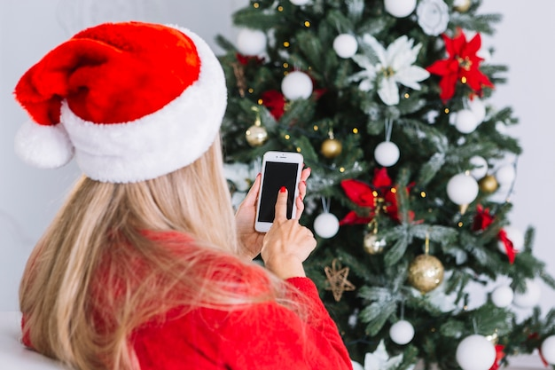 Woman in santa hat with phone
