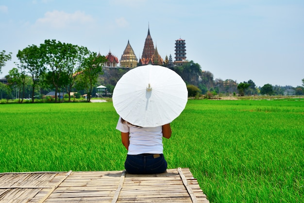 The woman sat facing the back of a white umbrella on a wooden bridge.