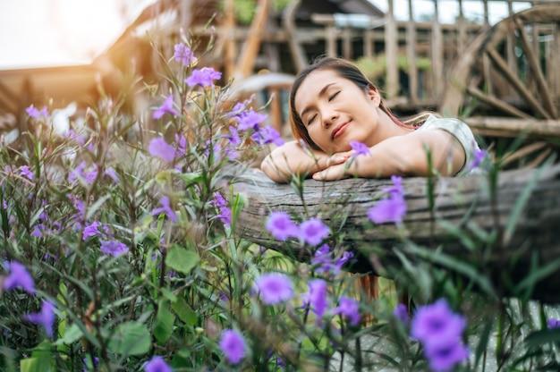 여자는 꽃밭에 행복하게 앉아 그녀의 손을 나무 울타리를 향해 누워