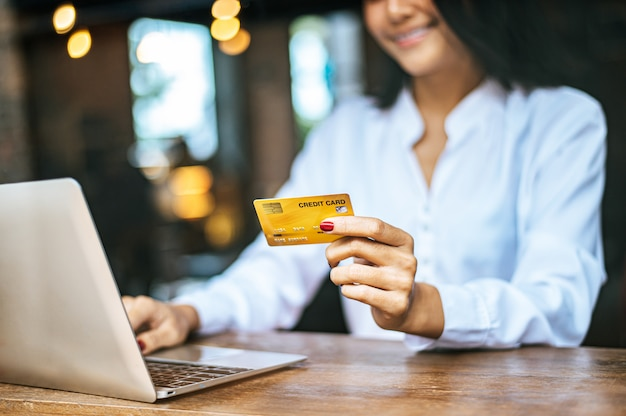 女性はラップトップで座って、カフェでクレジットカードで支払い
