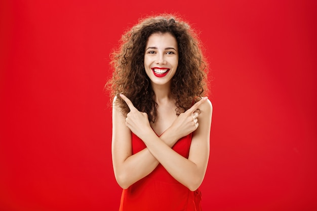 エレガントな赤いイブニングドレスでのんきで幸せな立ちを感じてどんな決断にも満足している女性...