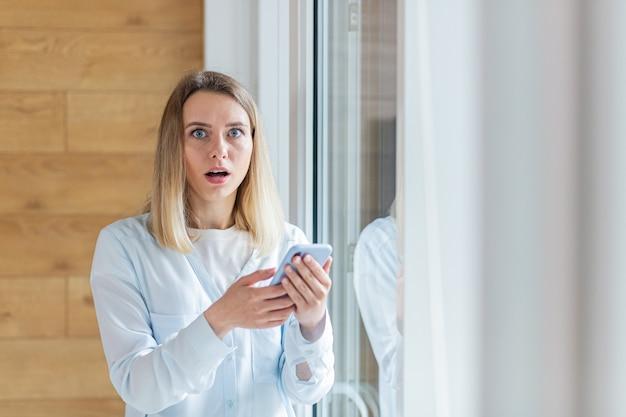 女性はオフィスや自宅の窓際に立っているスマートフォンで悪いニュースを見ました