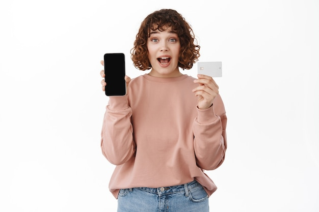 Woman say wow, show empty smartphone screen and credit card, gasps excited, looking at camera happy, standing on white